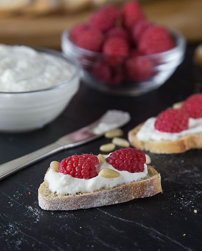 crostini with ricotta cheese and pine nuts with bowls of cheese and raspberries in the back