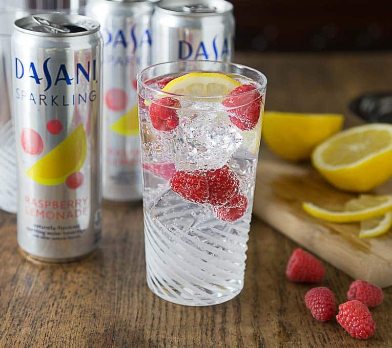 cans of sparkling water and a glass of mocktail with fruit
