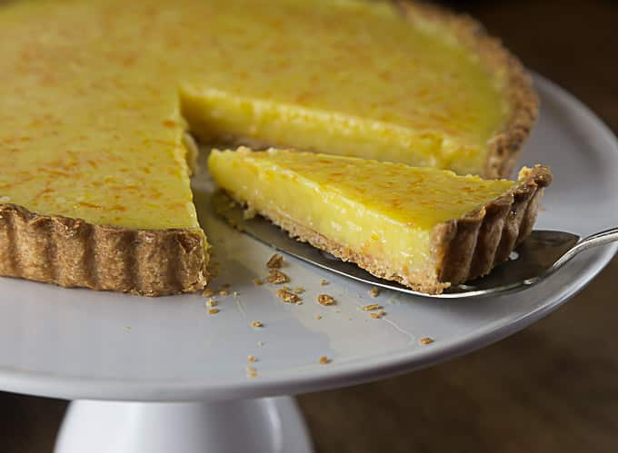 a lemon tart on a white tray with a slice being removed