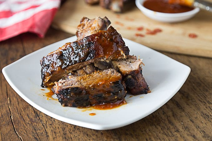 a plate of grilled ribs with bbq sweet and spicy bbq sauce
