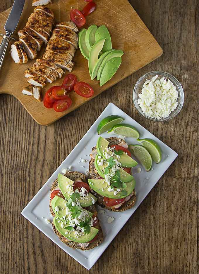 an open faced sandwich with avocado and cheese and a cutting board with sliced chicken and tomatoes and a bowl of cheese on the right