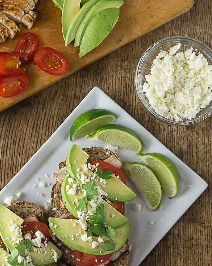 a close up of an avocado chicken open faced sandwich and a cutting board with avocado , tomato and a bowl of cheese on the right