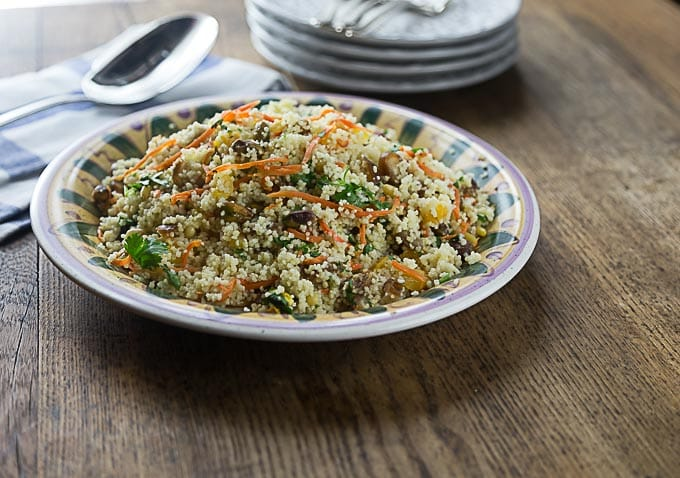 a plate of cous cous salad with carrots, dates, and greens with a stack of plates behind