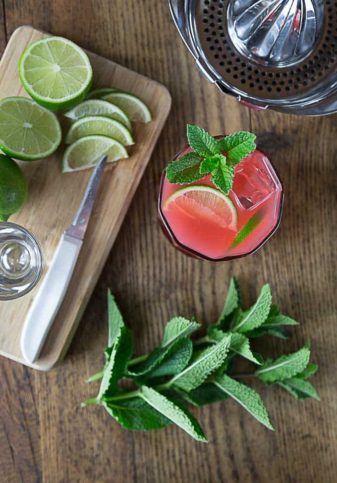 sliced limes on a cutting board, a juicer, a pink cocktail, and mint leaves
