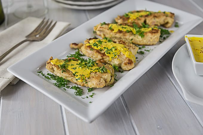 seared chicken breasts on a plate all topped with yellow creme sauce and parsley