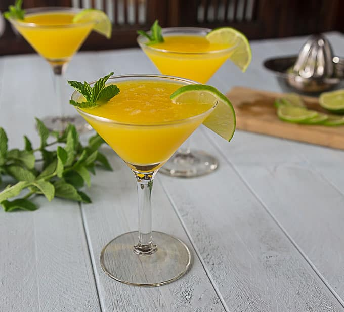 three martini glasses with mango cocktail and mint on the table.