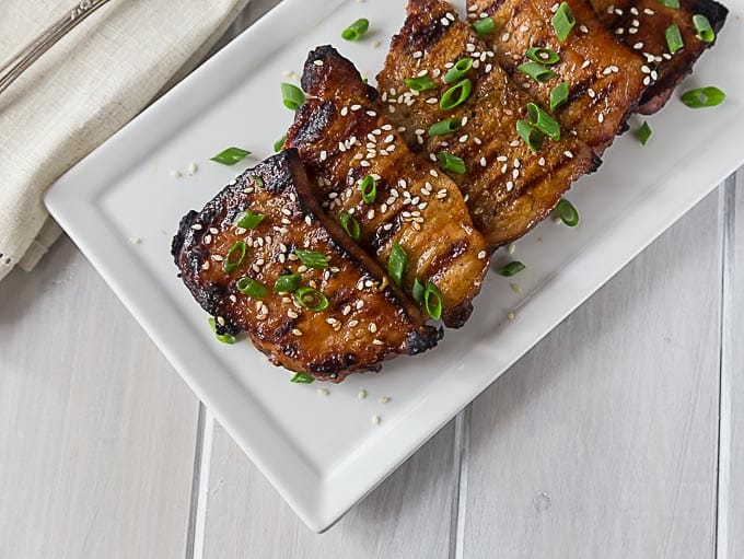 a white plate of grilled korean pork chops topped with sesame seeds and green onions