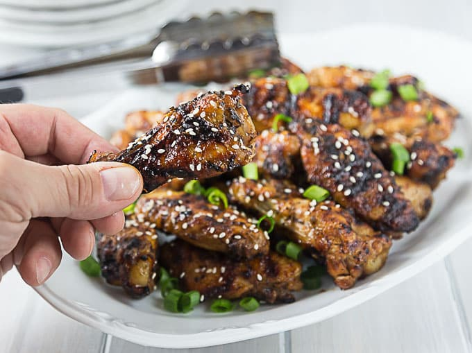 a plate of grilled thai chicken wings with a hand holding one in front