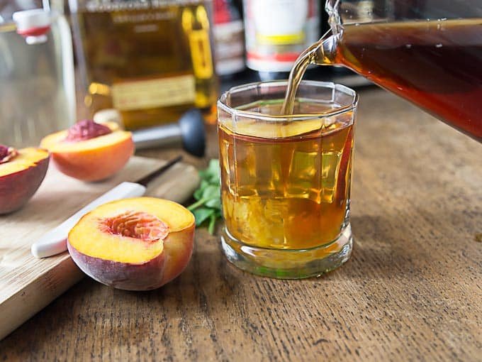 Enjoy a refreshing bourbon peach tea smash. I love local peaches in this is a delicious cocktail! | ethnicspoon.com