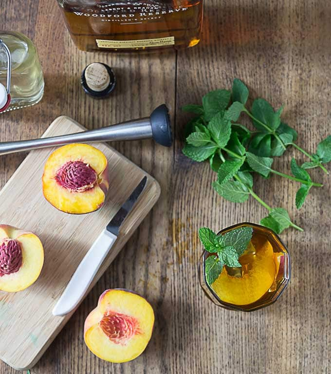 Bourbon peach tea smash cocktail with rosemary infused simple syrup. Muddle some peach slices add simple syrup, bourbon and tea. Delicious! | ethnicspoon.com