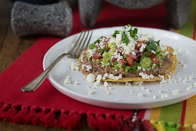 Enjoy a refried bean tostata with fresh pico de gallo, guacamole and queso fresco! These are a fast and delicious weeknight meal! Top off with your favorite salsa or hot sauce! | ethnicspoon.com