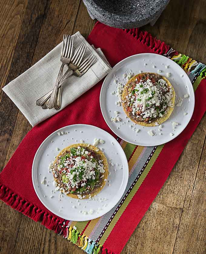 two white plates with tostadas on a red placemat with forks and a napkin on the left