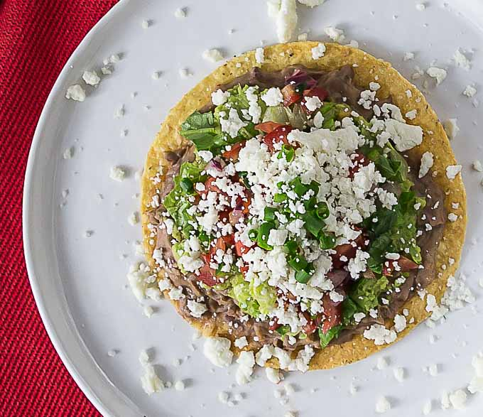a tostada on a white plate with crumbled cheese, beans, lettuce, and tomato