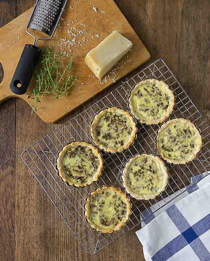 mushroom tarts on a rack next to a cutting board with cheese and thyme
