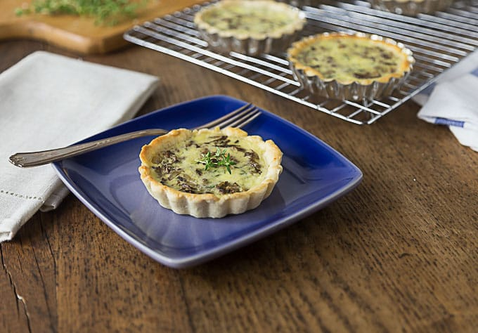a mushroom tart on a plate with a fork