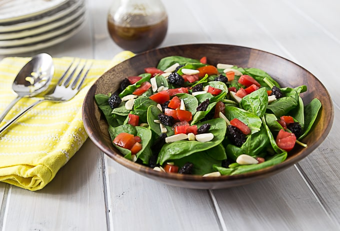 a spinach salad in a wooden bowl topped with tomatoes, raisins, and almonds with cutlery on the left