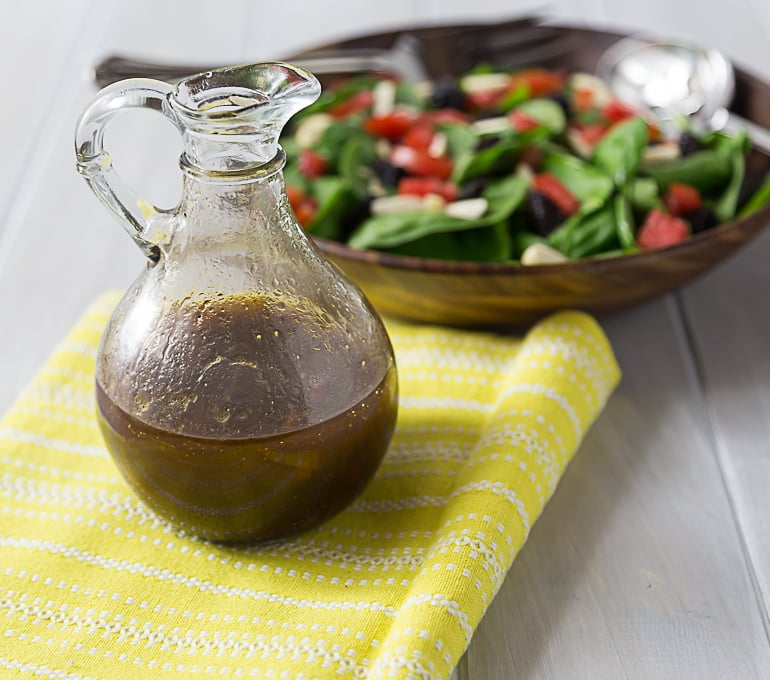 a jug of balsamic dressing on a yellow napkin with a salad in the back