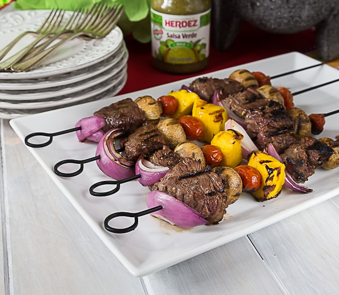 a white plate with beef kebabs on metal skewers with a stack of plates and forks in the back