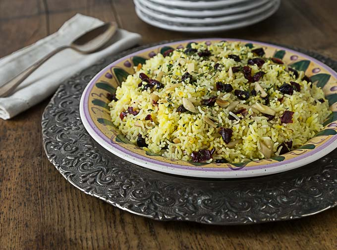 a sideview of a plate of saffron rice with craisins and almonds on a metal charger with a spoon on the left