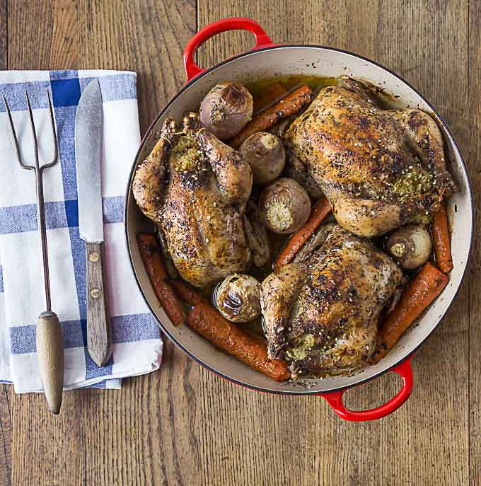 roasted cornish hens, carrots, and potatoes in a dutch oven with a fork and knife on the left