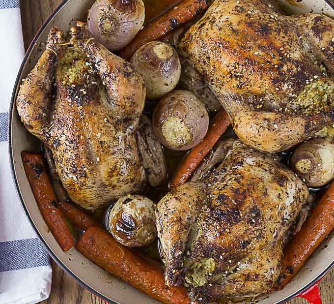 a closeup of roasted cornish hens, carrots, and potatoes with a blue and white napkin on the left