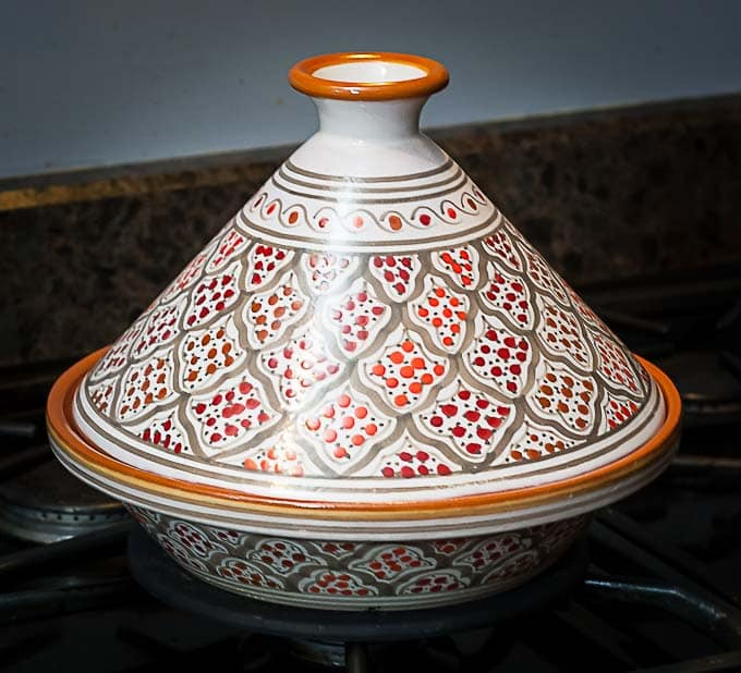 an orange and red tagine on the stove