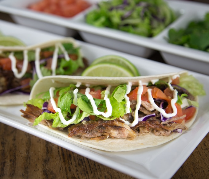 a closeup of a pork carnita taco with lettuce, sour cream, tomato and lime wedges