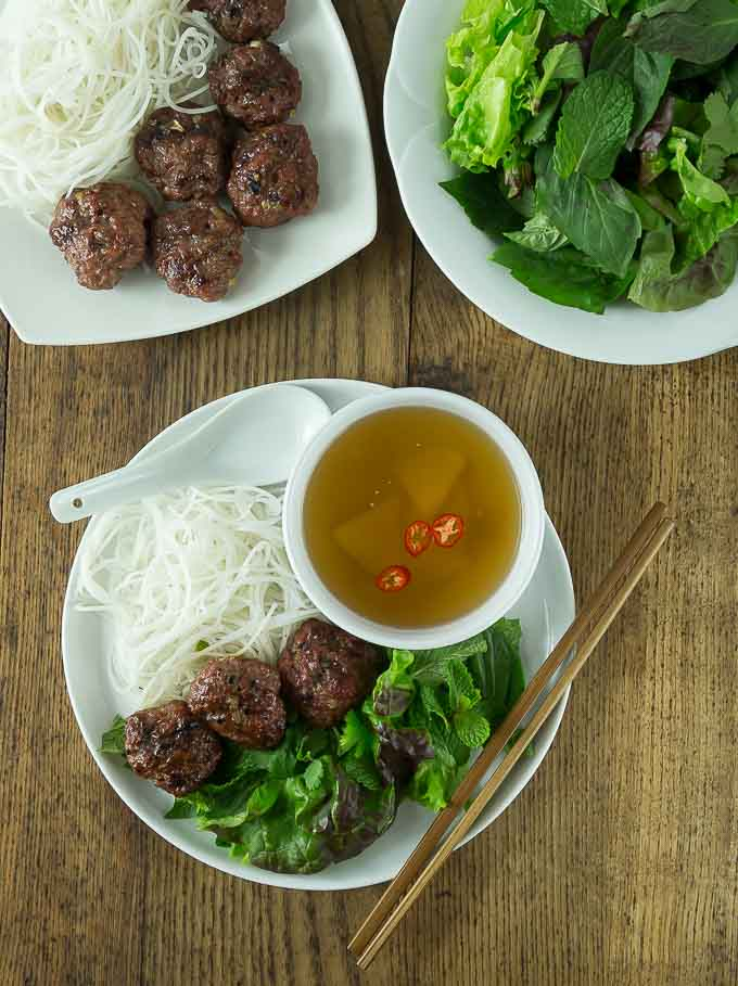 plates of meatballs, greens, noodles and broth