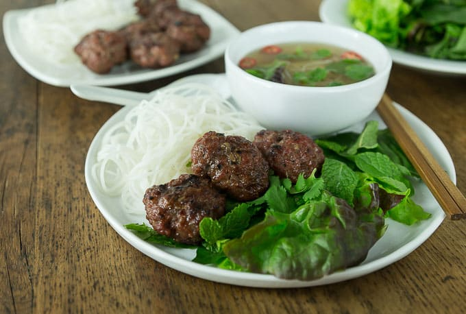 a plate of vietnamese rice noodles, meatballs, salad greens, and broth