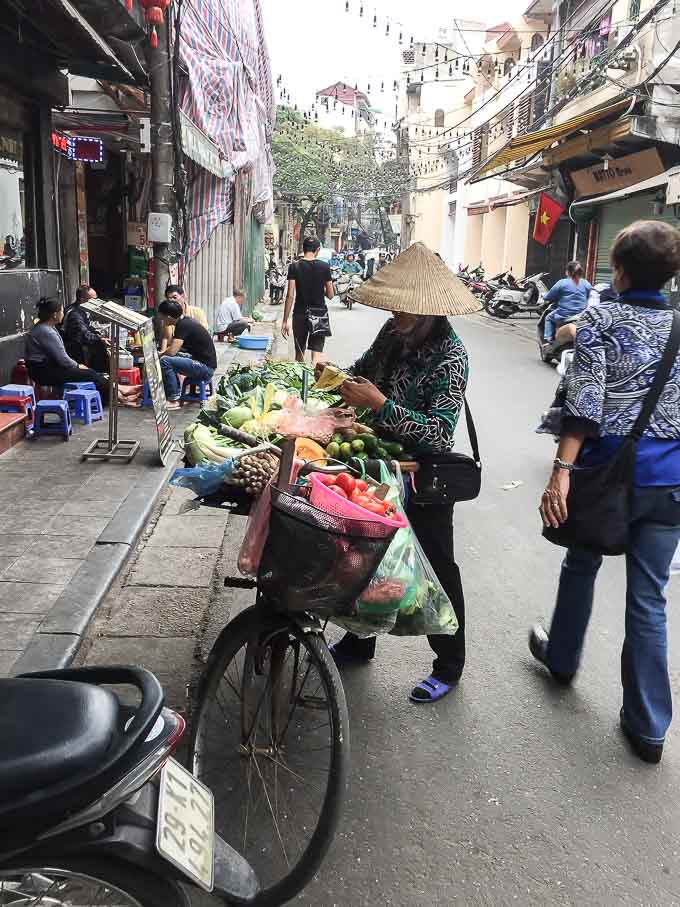 a lady selling fruit on the streets of Hanoi