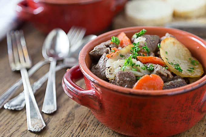 a red bowl of french beef stew with forks and spoons on the left