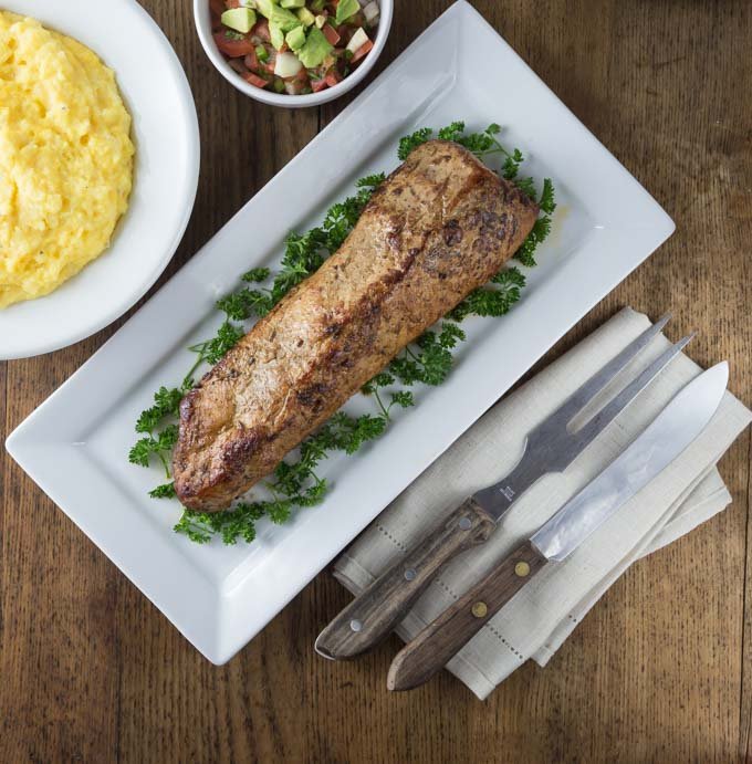a roasted pork loin on a plate next to a fork and a knife with parsley and a bowl of grits and pico de gallo above