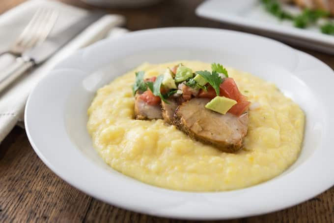 a white bowl of grits with sliced pork