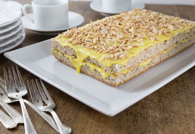 a slab of almond cake with yellow frosting and almond pieces and forks on the left