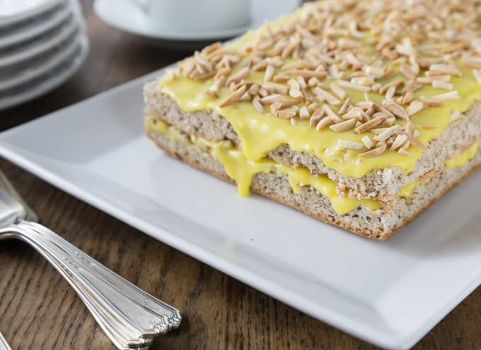 a white plate with Swedish almond cake with yellow frosting and almond pieces