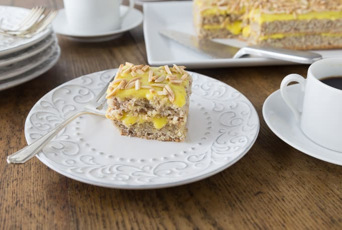 Try this Swedish almond cake topped with toasted almonds with you next cup of coffee! Light and airy Swedish almond cake makes a wonderful dessert your family will love! A nice meringue is folded into ground almonds and flour. Once it is baked you add a creamy almond custard like filling and topping. | ethnicspoon.com