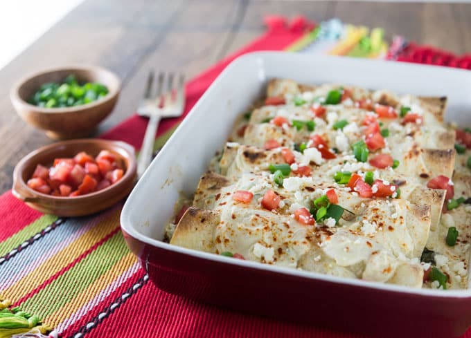 a baking dish of chicken enchiladas in white sauce tipped with tomatoes and jalepenos with two small bowls of toppings on the left