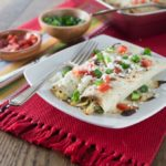 A photo of two chicken enchiladas on a plate with tomato and green onions.