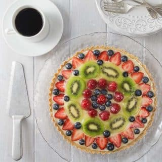 Make this for your next holiday party! The best ever fruit tart from scratch and simple to make! This has a creamy vanilla filling with a nice crunchy shortbread crust topped off with fresh fruit! Delicious! You are going to love the French patisserie style tart! It's so simple to make, bake the shortbread crust, whip together the filling and add to the crust and add the fruit. | ethnicspoon.com