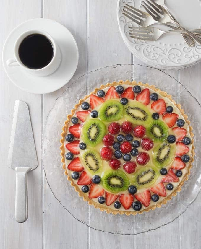 A large fruit topped dessert on a glass plate with forks, a cake knife and coffee