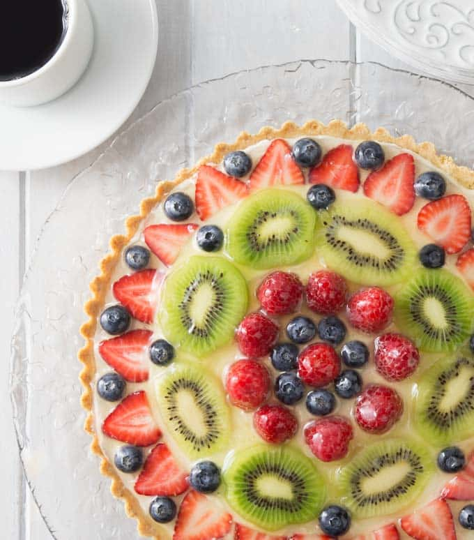 a fruit topped tart on a glass plate with coffee on the left