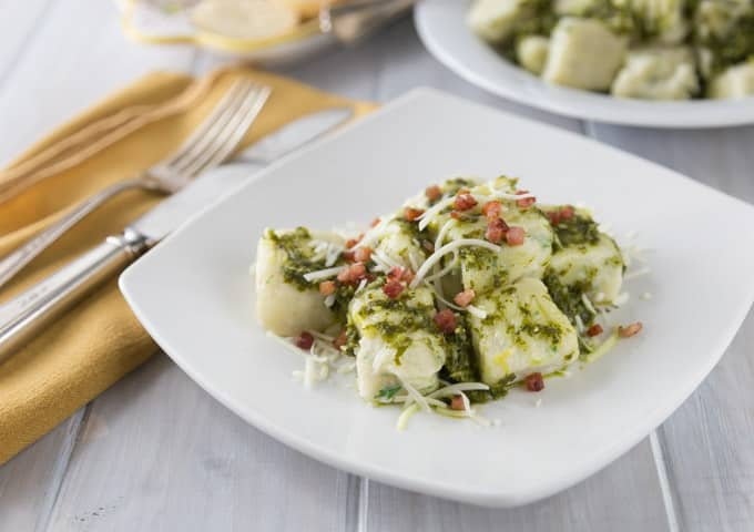a plate of ricotta gnocchi with pesto and bacon with a yellow napkin and cutlery on the left
