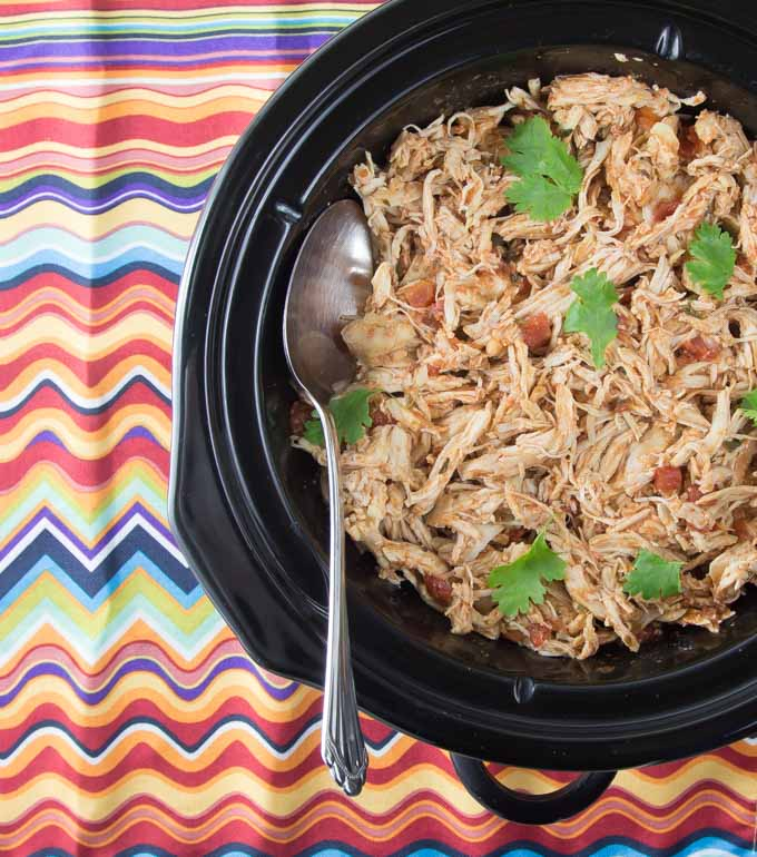 chicken tinga in the slow cookers with a spoon on a colorful napkin