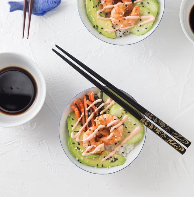 Healthy and easy to make spicy shrimp sushi bowls with avocado, carrots, nori, sticky rice, cucumber slices and sprinkled with black sesame. Top this off with a spicy sriracha sour cream sauce! Dip in some tasty soy sauce and enjoy. | ethnicspoon.com