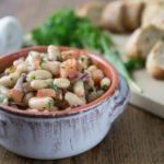 bean salad in a white bowl with bread