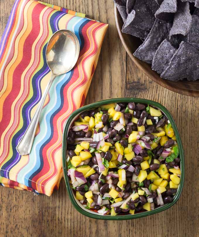a bowl of mango black bean salsa and a bowl of chips with a colored napkin and spoon on the left
