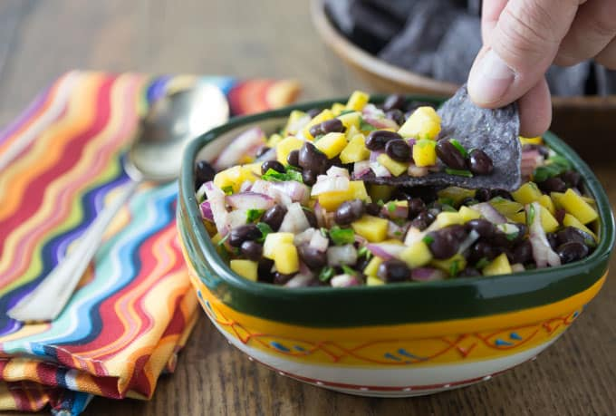 Need a dish for a summer picnic? Try this super easy mango black bean salsa! This is my go-to dish to bring to summer picnics. If you can chop and stir this is the salsa for you! I love the sweet, savory and spicy flavors this dish brings. | ethnicspoon.com