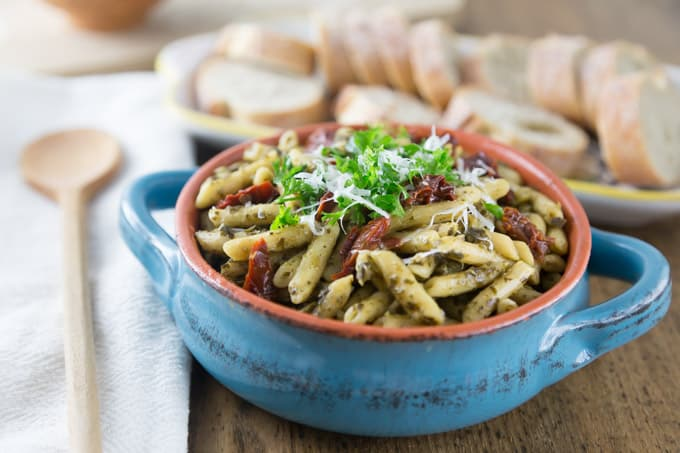 a blue crock of pesto pasta with sundried tomatos and parsley with sliced baguette in the back