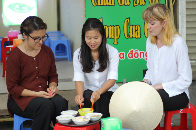 a group of tourists trying Vietnamese dessert with a local