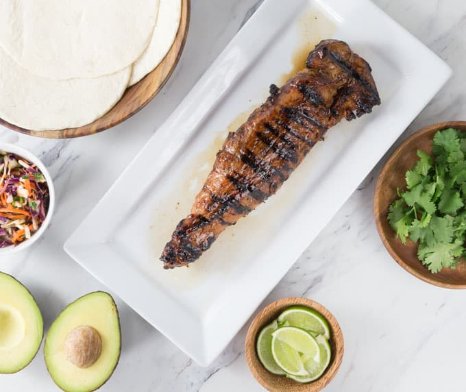 a grilled pork tenderloin on a white plate with taco ingredients around it